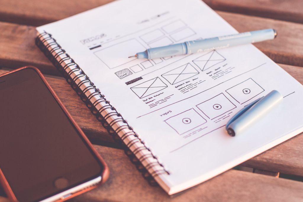 Smartphone et cahier avec un dessin de wireframes